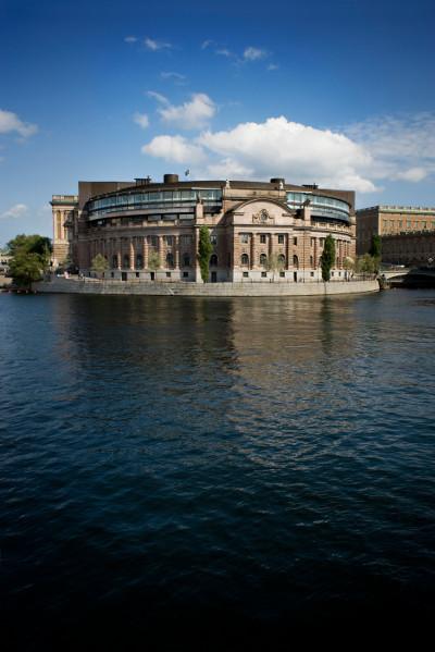 Västra riksdagshuset speglas i Strömmen. Blå himmel och vita moln.